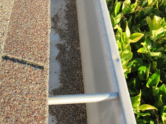 Rain gutters full of loose shingle granules from the roof.