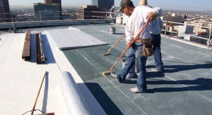 Men working on the roof of a large commercial building.