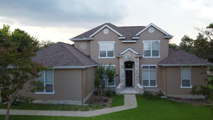 Two story stone and stucco house with an asphalt shingle roof in a nice neighborhood.