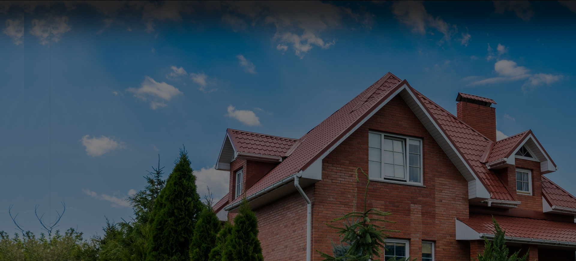 Nice brick home with an orange tile roof against a clear sky.