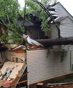 Massive storm damage to a house with a fallen tree on it.