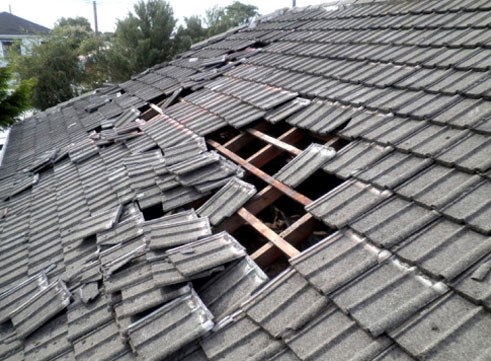 Serious hail damage to a grey tile roof.