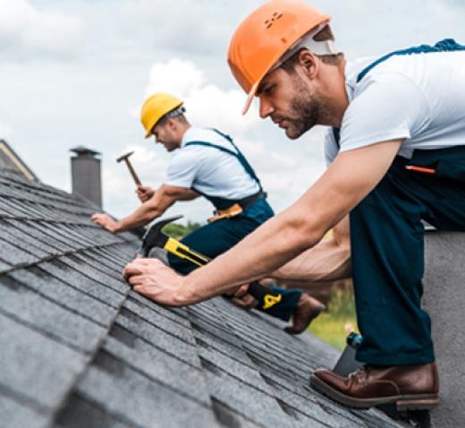 Men in hard hats working on a slanted asphalt shingle roof.
