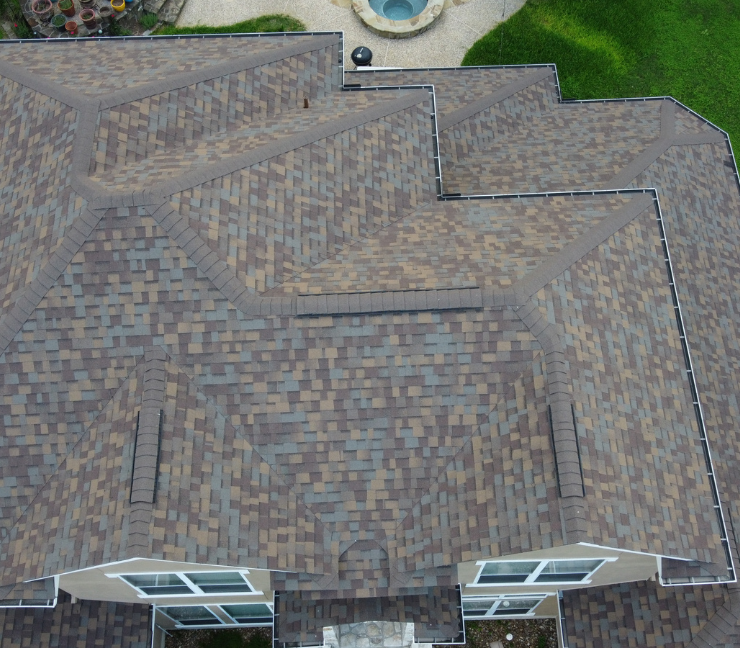 Aerial view of a very nice asphalt shingle roof on a large expensive stucco house.