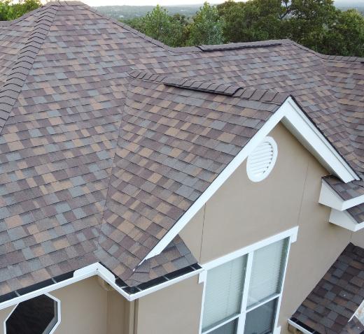 Very nice asphalt shingle roof on a stucco house viewed from a dramatic slant.