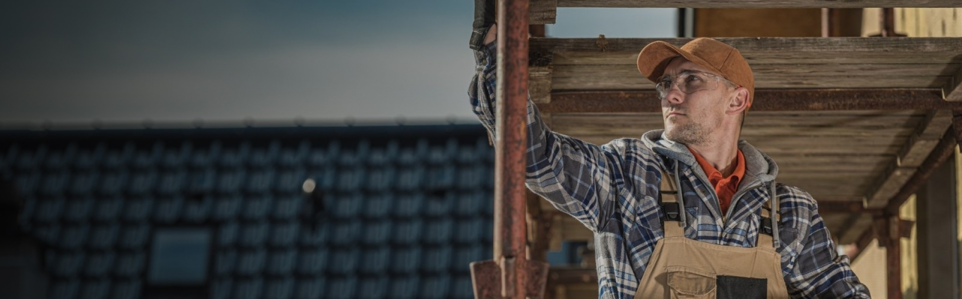 Man in a brown hat and blue plaid shirt holding a pipe while working on a tile roof.