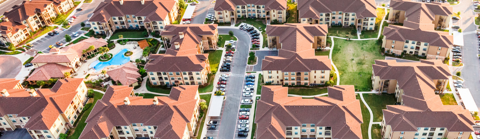 An apartment complex with lots of asphalt roofs shot from above.