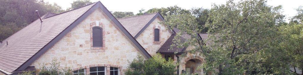 Background image of a nice stone house with an asphalt shingle roof.
