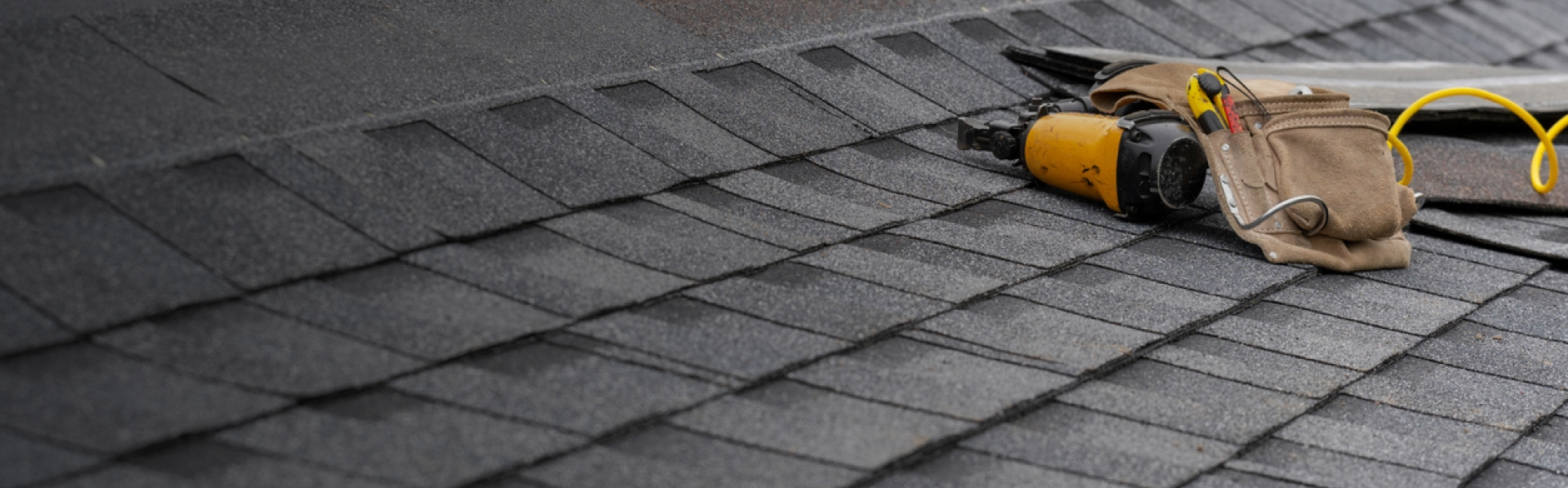 A well built asphalt roof with tools laying on it.