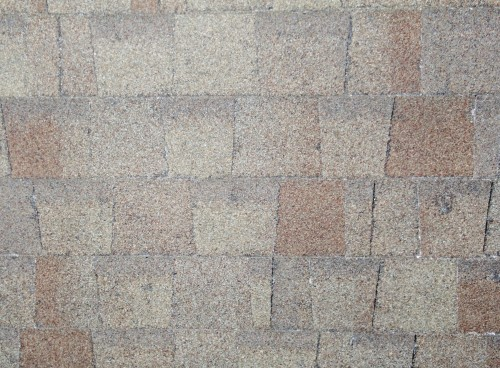 Hail impact on brown architectural shingle.