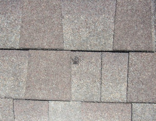 Close up of a hail impact to a roof shingle.