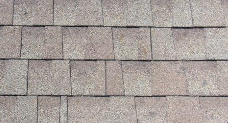 Close up of hail damage to architectural shingles and ridge vent.